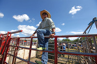 Cowboys on the fence of the bull pen under a clear summer sky.